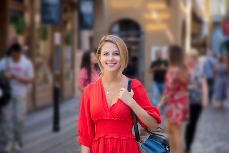 Beautiful redhead girl in red dress travel in Prague, city streets Banque d'images