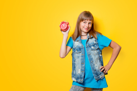 portrait of young smiling teenage girl with alarm clock on yellow background Stock Photo