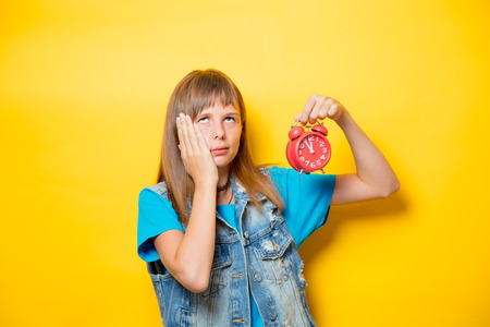 portrait of young teenage girl with alarm clock on yellow background