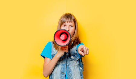 portrait of young teenage girl with megaphone on yellow background Banque d'images