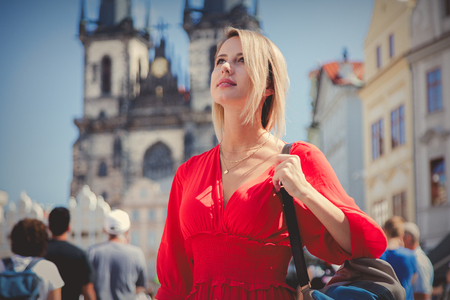 Beautiful redhead girl in red dress travel in Prague, city streets 写真素材