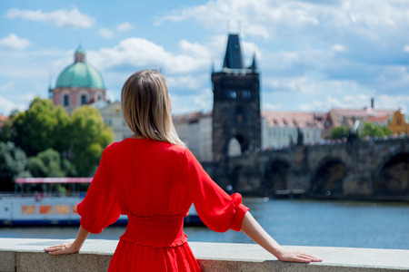 Beautiful girl in red dress travel in Prague, city streets