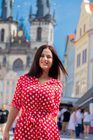 Beautiful brunette girl in red dress travel in Prague, city streets Reklamní fotografie