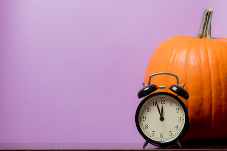 one orange pumpking and vintage alarm clock on purple background