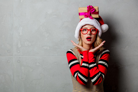 Young girl with Christmas gift box over head on grey background Stock Photo