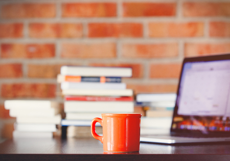 Cup of coffee and laptop computer on a table with books on brick wall background