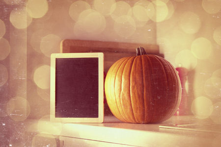 Beautiful Autumn pumpkin and blackboard menu on a table in kitchen