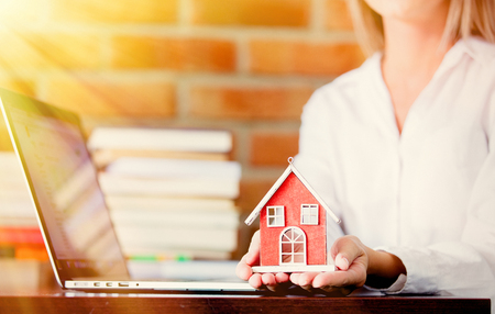Young realtor sitting on a table with laptop computer and books and holding a house. Brick wall on background