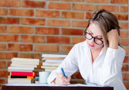 Young businesswoman sitting on a table with laptop computer and books. She had migraine. Brick wall on background