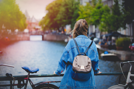Young girl in jeans jacket and backpack at bridge in Amsterdam street. Holland, Netherlands. Autumn season 免版税图像