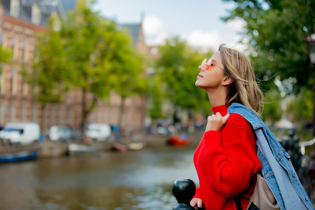 Young girl in red sweater and orange sunglasses with backpack at bridge in Amsterdam street. Holland, Netherlands. Autumn season