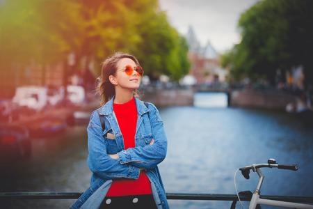 Junges Mädchen im roten Pullover und in der orange Sonnenbrille mit Rucksack an der Brücke in der Amsterdamer Straße. Holland, Niederlande. Herbstsaison
