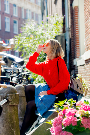 Young girl in sunglasses and red sweater with backpack sitting at street in Amsterdam. Holland, Netherlands. Autumn season