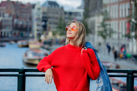 Young girl in red sweater and orange sunglasses at bridge in Amsterdam street. Holland, Netherlands. Autumn season Stock Photo