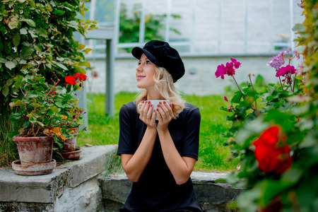 Young style girl in black dress and hat with cup of coffee in a green autumn season garden in Belgium.