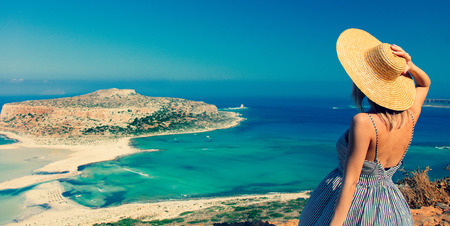 Young redhead girl in hat and dress with sea coastline on Balos, Crete, Greece Imagens - 109135987