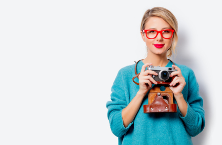 Portrait of a beautiful white smiling woman in blue sweater with vintage camera on white background, isolated.