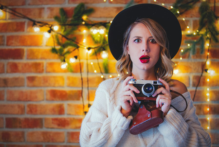 Portrait of a young cozy woman in white sweater with vintage camera and Christmas lights and pine branch
