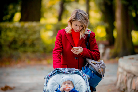 Young woman strolling in a park with stroller and a child in autumn season 版權商用圖片