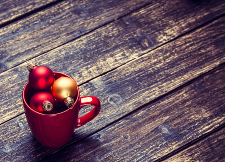 red Cup with christmas baubles on wooden table