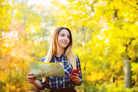 Junges weißes Mädchen, das eine mobile Anwendung und eine Karte für eine Navigation in einem Park verwendet. Herbstzeit Standard-Bild