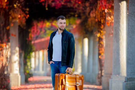 Young white guy with suitcase on red grape alley. Autumn season 写真素材 - 110076153