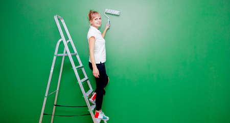 Young woman with paint roller and ladder in own house after painting a room. Real people Reklamní fotografie
