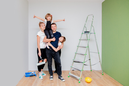 young family, parents and children are paint a new room in their apartment Banque d'images - 111775472