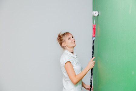 Young woman with paint roller in own house after painting a room. Real people Imagens