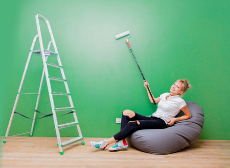 Young woman with paint roller have a rest in own house after painting a room. Real people