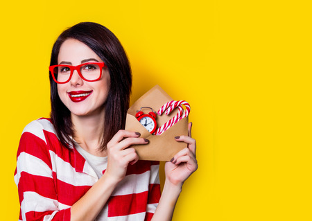 Young woman with envelope full of christmas gifts on yellow background