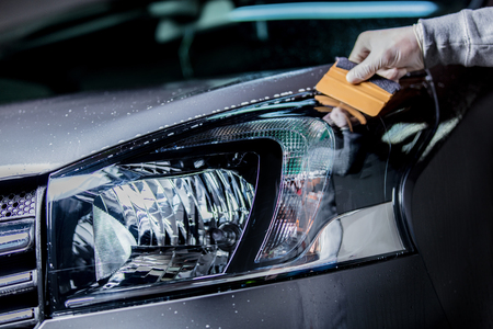 Man's hand washing a car headlight on car wash 스톡 콘텐츠
