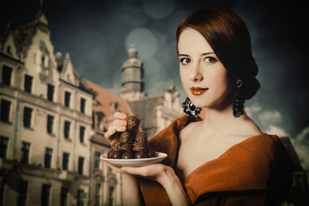 Beautiful redhead woman with candy and Brussels in the background . Photo in retro style. Stock Photo