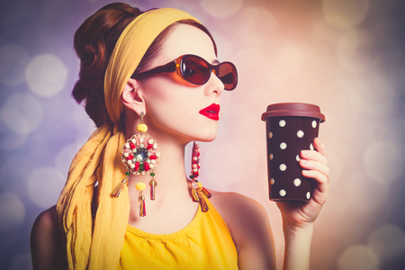 Style redhead woman in yellow clothes with coffee. Photo with bokeh on background. Stock Photo
