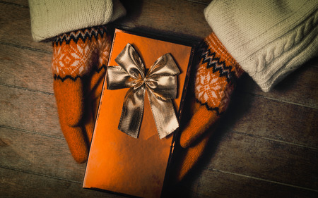 Hands in mittens holding gift box. Photo in old color imagestyle.