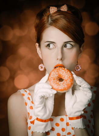 Beautiful redhead woman with donut. Photo in retro style with bokeh at background. 免版税图像