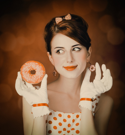Beautiful redhead woman with donut. Photo in retro style with bokeh at background. Stock Photo