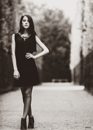 Beautiful woman in black dress in versailles gardens. Image in black and white color style