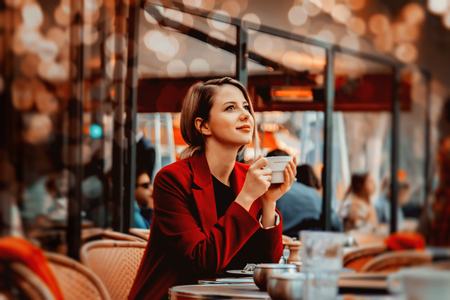 Style redhead girl in red coat with cup of coffee in parisian cafe. Autumn season time