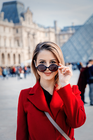 Style redhead girl in red coat and bag on parisian street in autumn season time