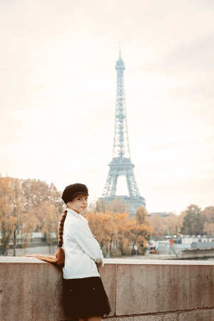 Style young girl with long hair at parisian street. Eiffel tower tower on background
