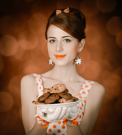 Beautiful redhead woman with coockie. Photo in retro style with bokeh at background.