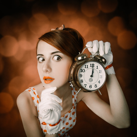 Surprised redhead woman with clock. Photo in retro style with bokeh at background.