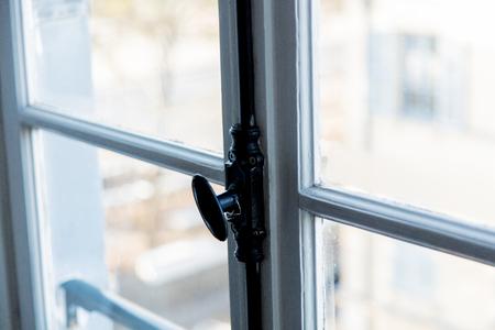Vintage french black window handle on white wodow.