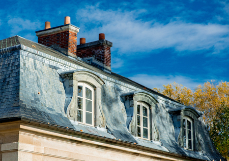 View at french vintage roof with window on blue sky background in Versailles, France Foto de archivo