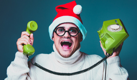 Funny man in red Christmas hat and white sweater and glasses with dial phone and handset Stock Photo