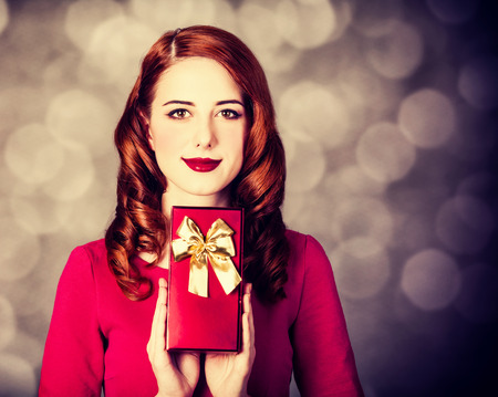 Style redhead woman in red dress with gift box on ray background with bokeh Фото со стока