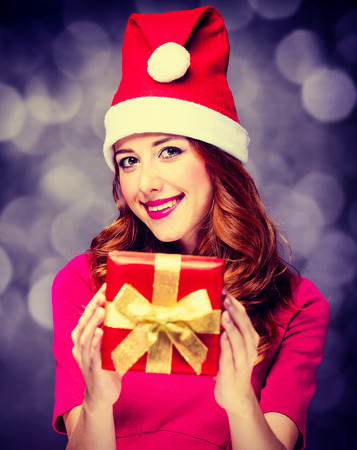 Funny redhead girl in red dress and hat with Christmas gift box on gray background Фото со стока
