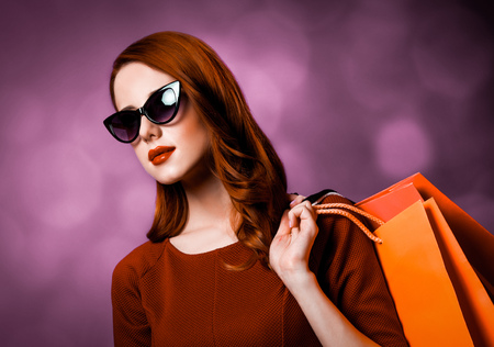 Redhead woman in sunglasses with shopping bags on purple background. Фото со стока