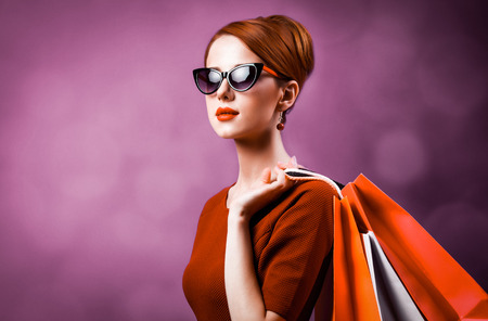 Redhead woman with shopping bags on purple background.